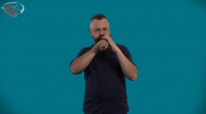 A man in black shirt signs about blood pressure in front of a teal background